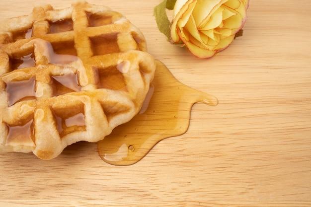 Um pedaço de waffle fresco com mel em uma placa de madeira.