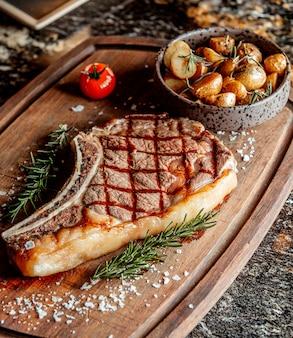 Um pedaço grande de carne frita gordurosa para bife com batatas
