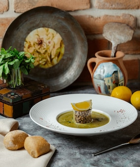 Um pedaço redondo de comida tradicional russa com molho oleoso e uma fatia de limão por cima