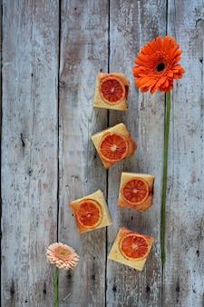 Um pedaços de bolo de laranja de sangue e flor vermelha em fundo de madeira