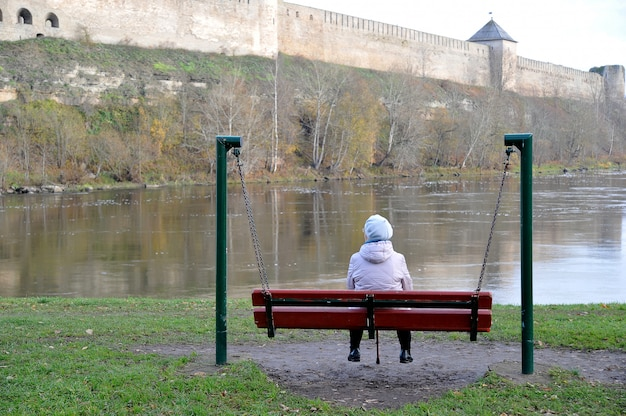 Um pensionista de mulher idosa sentada num banco e olhando para o rio e a antiga fortaleza