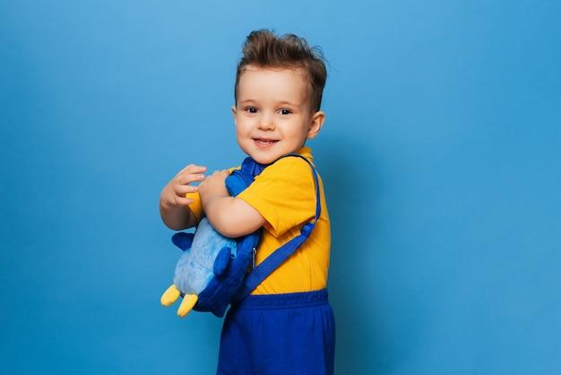 Um pequenino fofo abraços com sua mochila em um fundo azul. garoto engraçado
