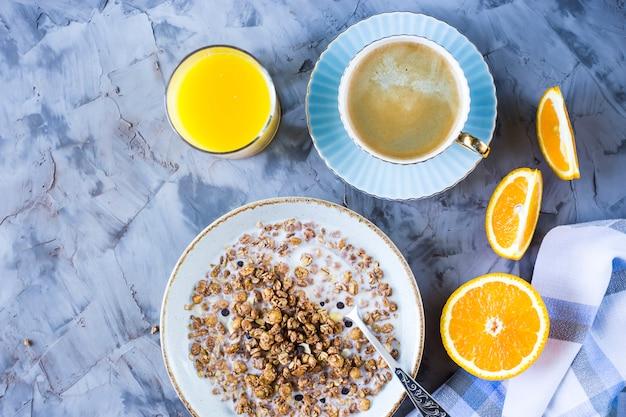 Um pequeno-almoço saudável de muesli de chocolate com café, laranja e suco