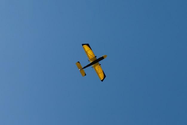 Um pequeno avião com asas amarelas no ar.