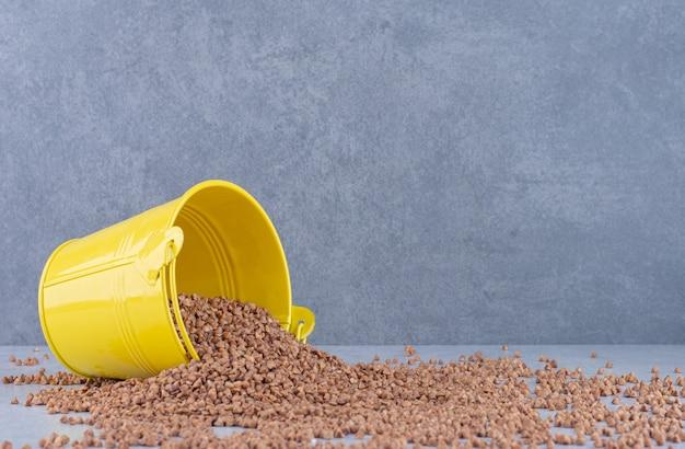 Um pequeno balde caiu em cima de um monte de trigo sarraceno espalhado na superfície de mármore