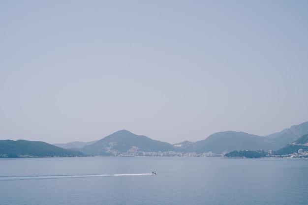 Um pequeno barco a motor navega no mar contra a costa montenegrina perto de budva