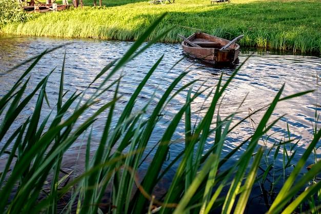 Um pequeno barco a remo de madeira com um fundo quebrado em um lago calmo perto da costa.