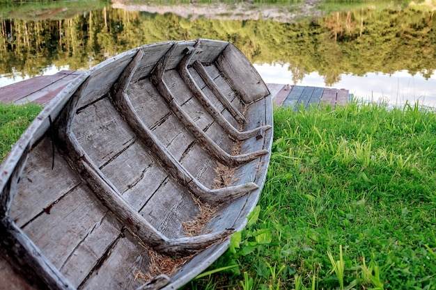 Um pequeno barco a remo de madeira seca na praia, perto de um lago calmo no qual a floresta é refletida.