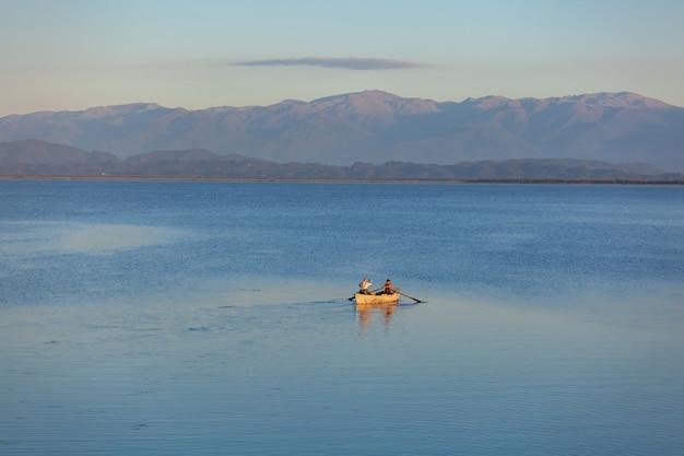 Um pequeno barco e os pescadores no lago paliastomi. poti. geórgia. natureza.