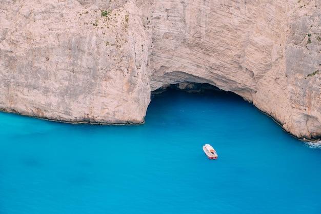 Um pequeno barco flutua perto da costa rochosa no mar azul-turquesa