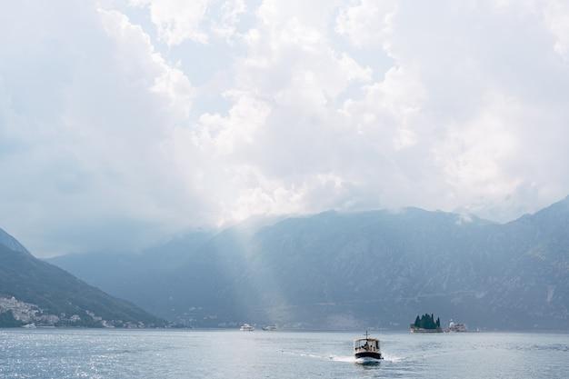 Um pequeno barco turístico navega na baía de kotor com as ilhas ao fundo perto de perast em