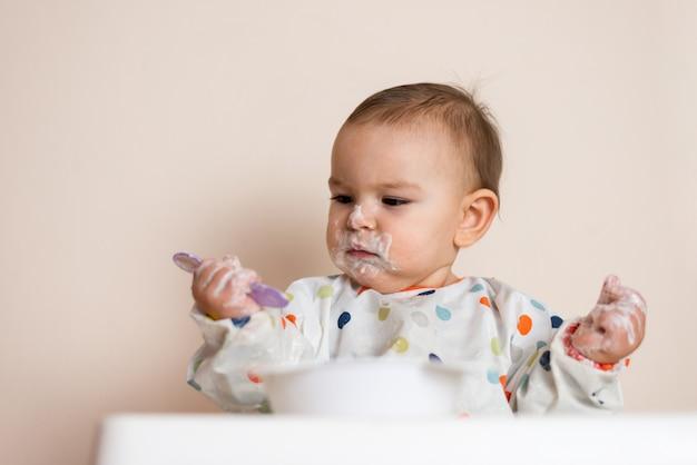 Um pequeno bebê comendo seu jantar e fazendo uma bagunça com iogurte e cereais