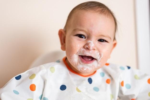 Um pequeno bebê comendo seu jantar e fazendo uma bagunça