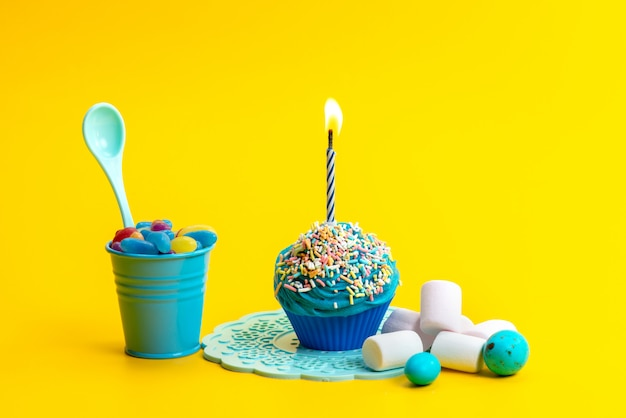 Um pequeno bolo de aniversário de frente para a cor azul com marshmallows e doces na cor amarela do biscoito da mesa
