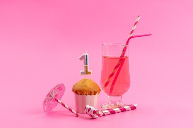 Um pequeno bolo de aniversário de vista frontal com apito de aniversário rosa, suco com canudo em rosa, cor de festa de biscoito