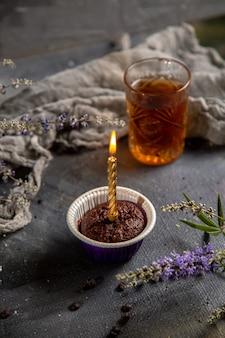 Um pequeno bolo de chocolate com vela e chá na mesa cinza bolo de biscoito de biscoito chá de chocolate com vista frontal