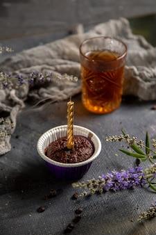 Um pequeno bolo de chocolate com vela e chá na mesa cinza.