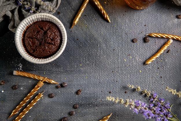 Um pequeno bolo de chocolate com velas e flores roxas e chá na mesa cinza.