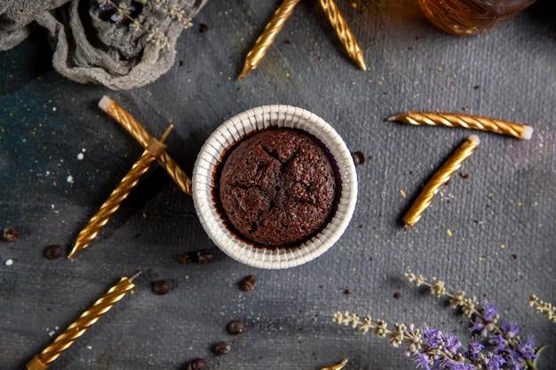 Um pequeno bolo de chocolate com velas, flores roxas e chá na mesa cinza.