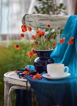 Um pequeno buquê de papoulas vermelhas em um vaso azul na cadeira vintage. papoulas e café.