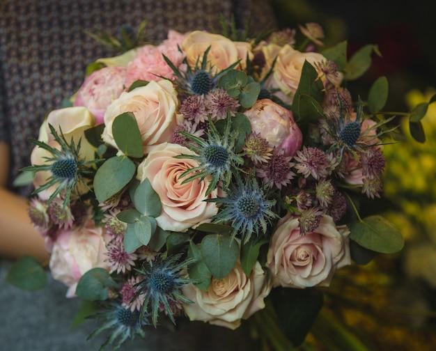 Um pequeno buquê de rosas e flores decorativas nas mãos de uma mulher.
