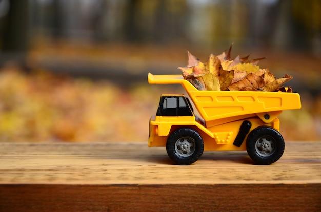 Um pequeno caminhão amarelo de brinquedo é carregado com trabalhos leavessonal caídos amarelos