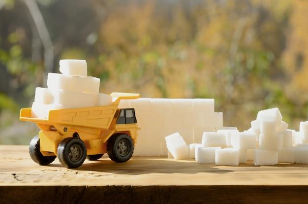 Um pequeno caminhão de brinquedo amarelo é carregado com cubos de açúcar branco perto dos restos de açúcar.