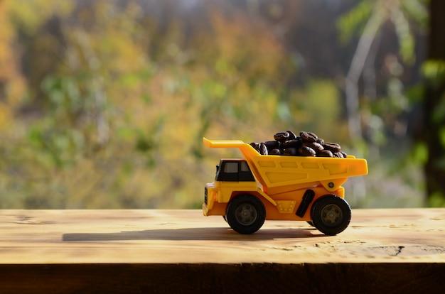 Um pequeno caminhão de brinquedo amarelo é carregado com grãos de café marrons.