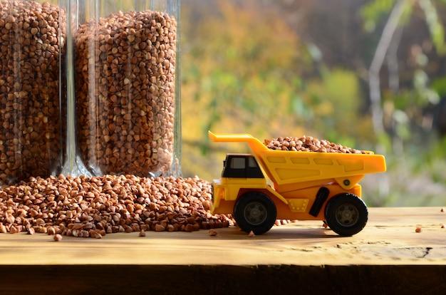 Um pequeno caminhão de brinquedo amarelo é carregado com grãos marrons de libré de trigo mourisco