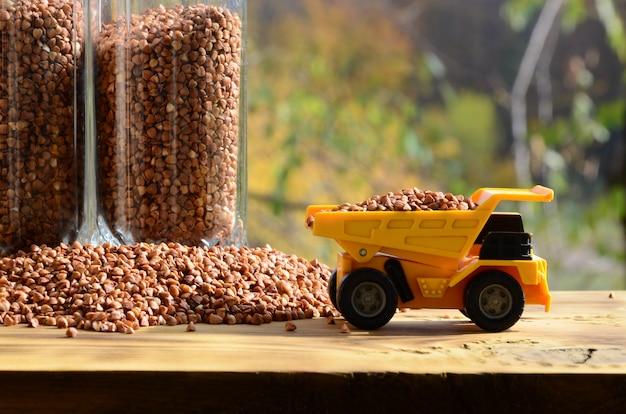 Um pequeno caminhão de brinquedo amarelo é carregado com grãos marrons de trigo mourisco ao redor da pilha de trigo mourisco e um copo de garupa.