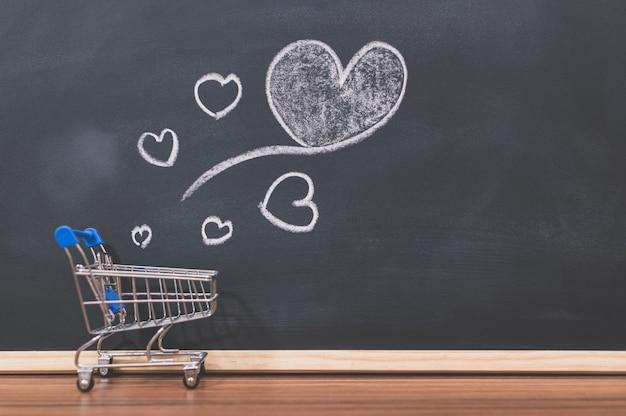 Um pequeno carrinho de compras e um coração em forma de quadro negro