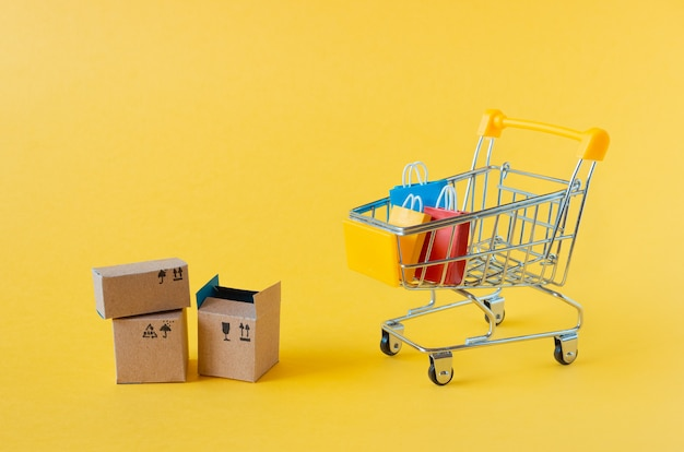 Um pequeno carrinho de supermercado com caixas e sacolas em amarelo