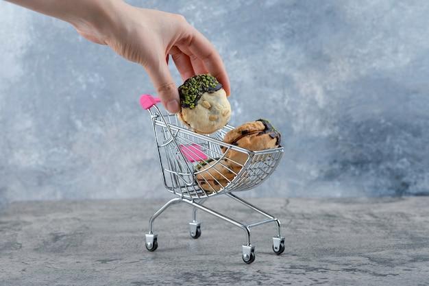 Um pequeno carrinho rosa de saborosos biscoitos com granulado em uma mesa de mármore.