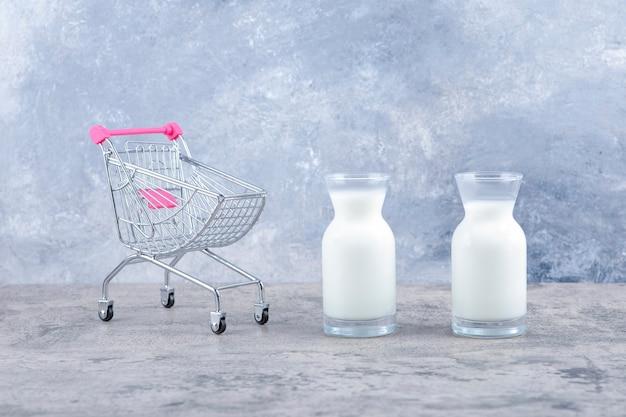 Um pequeno carrinho rosa vazio com jarras de vidro com leite fresco.