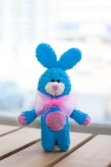 Um pequeno coelho azul de malha com gravata rosa na superfície de madeira. brinquedo de malha, feito à mão. amigurumi.