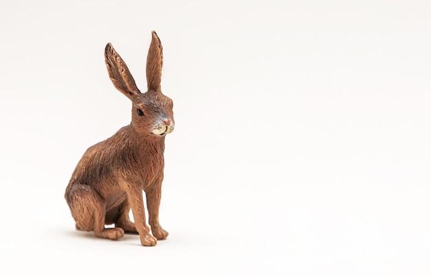 Um pequeno coelho de brinquedo é isolado em uma superfície branca