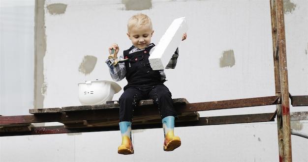 Um pequeno construtor com um capacete branco está sentado no andaime com um alicate nas mãos