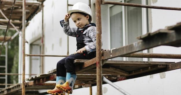 Um pequeno construtor com um capacete branco está sentado no andaime menino feliz balançando as pernas