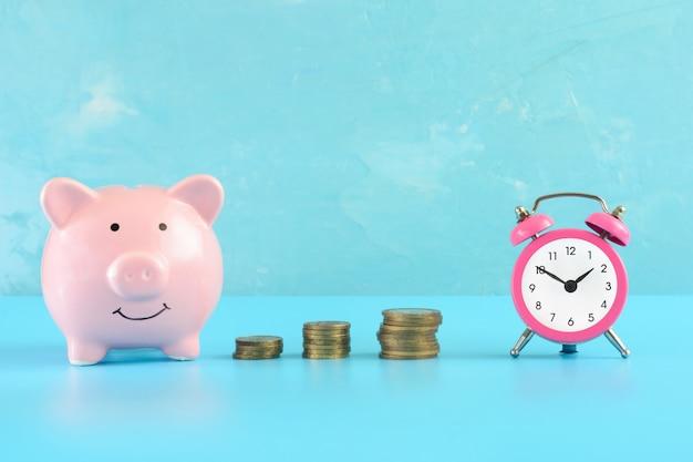 Um pequeno despertador rosa, uma pilha de moedas e um cofrinho em azul