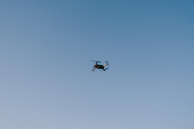 Um pequeno drone cinza voa no céu azul