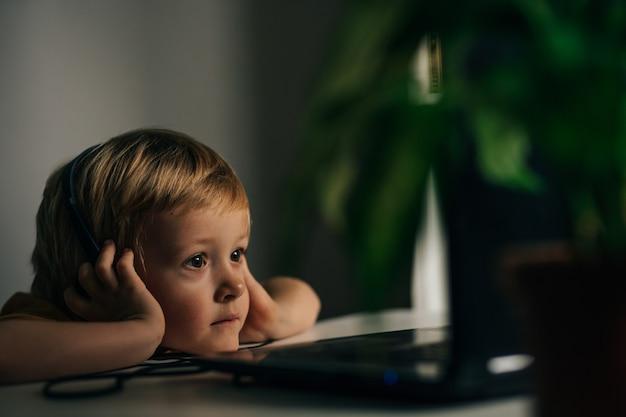 Um pequeno estudante interessado com fones de ouvido está sentado em sua mesa de casa e assistindo a um vídeo tutorial