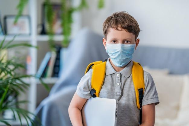 Um pequeno estudante usa máscara, proteção durante o vírus da coroa e gripe.