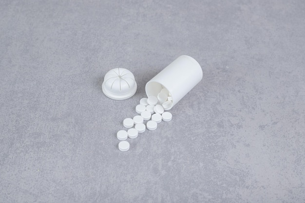Um pequeno frasco branco de comprimidos brancos em fundo cinza.