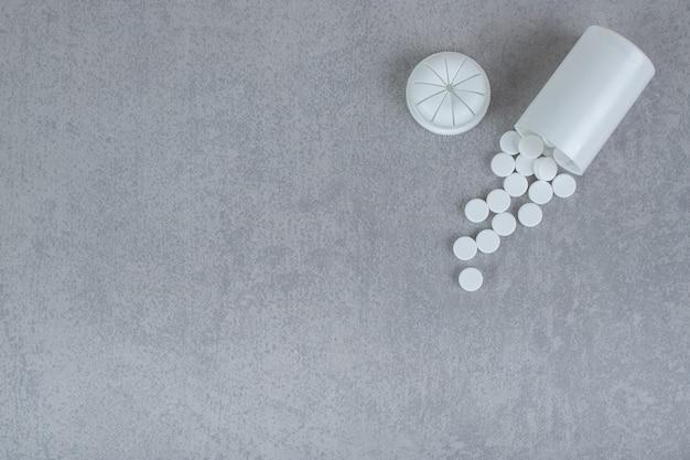 Um pequeno frasco branco de comprimidos brancos na superfície cinza