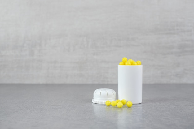 Um pequeno frasco branco de comprimidos de ácido ascórbico na superfície cinza