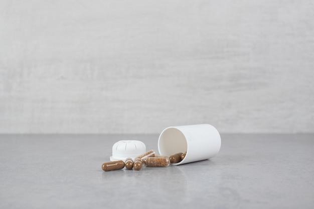 Um pequeno frasco branco de comprimidos marrons na superfície cinza