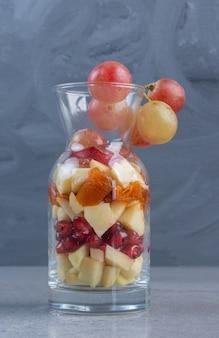 Um pequeno frasco cheio de uma variedade de frutas picadas em fundo de mármore.