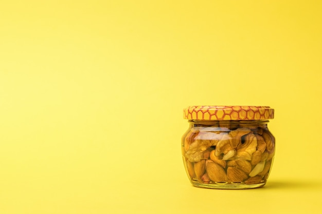 Um pequeno frasco de vidro com mel e nozes em um fundo amarelo.
