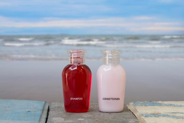 Um pequeno frasco de xampu e condicionador com mar na praia.