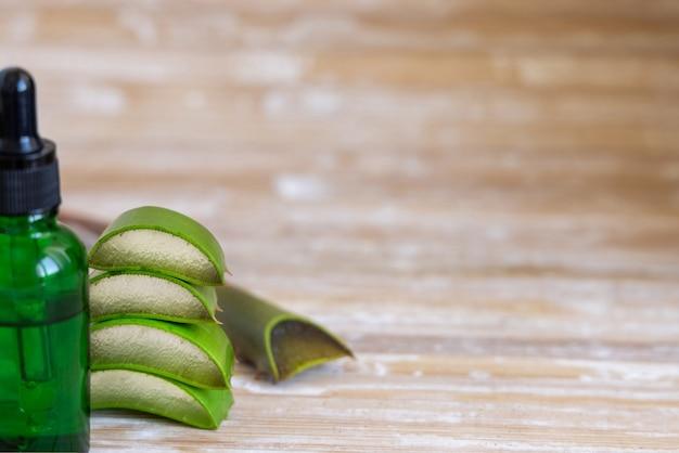 Um pequeno frasco verde com um conta-gotas e folhas cortadas de aloe vera de perto